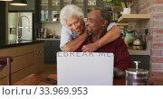 Купить «Senior African American husband and mixed race wife happily working on a laptop at home», видеоролик № 33969953, снято 19 февраля 2020 г. (c) Wavebreak Media / Фотобанк Лори