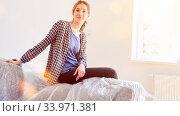 Junge Frau sitzt bei Umzug auf einem abgedeckten Sofa im neuen Eigenheim. Стоковое фото, фотограф Zoonar.com/Robert Kneschke / age Fotostock / Фотобанк Лори