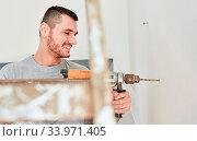 Купить «Junger Mann mit Bohrmaschine an der Wand beim Loch bohren bei der Renovierung», фото № 33971405, снято 3 июля 2020 г. (c) age Fotostock / Фотобанк Лори