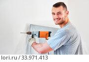 Купить «Junger Mann als Heimwerker mit Bohrmaschine beim Bohren von einem Loch in der Wand», фото № 33971413, снято 3 июля 2020 г. (c) age Fotostock / Фотобанк Лори