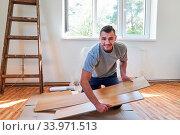 Купить «Mann als Heimwerker bei der Renovierung im neuen Haus oder Eigenheim beim Parkett verlegen», фото № 33971513, снято 3 июля 2020 г. (c) age Fotostock / Фотобанк Лори