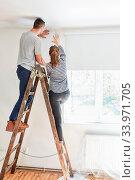 Junges Paar beim Tapezieren gemeinsam auf der Leiter bei der Renovierung von einem Haus. Стоковое фото, фотограф Zoonar.com/Robert Kneschke / age Fotostock / Фотобанк Лори