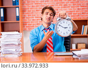 Купить «The young employee with excessive work sitting at the office», фото № 33972933, снято 4 июля 2020 г. (c) easy Fotostock / Фотобанк Лори