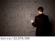 Купить «Young businessman in black suit standing in front of detailed calculations», фото № 33974189, снято 7 августа 2020 г. (c) easy Fotostock / Фотобанк Лори