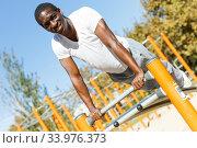 Купить «Active african american man doing workout at pull-up bar in park», фото № 33976373, снято 3 ноября 2018 г. (c) Яков Филимонов / Фотобанк Лори