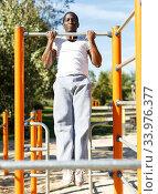 Купить «Active african american man doing workout at pull-up bar in park», фото № 33976377, снято 3 ноября 2018 г. (c) Яков Филимонов / Фотобанк Лори