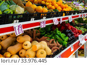 Large assortment of fresh colorful fruits and vegetables in wicker trays on shelves in supermarket. Стоковое фото, фотограф Яков Филимонов / Фотобанк Лори
