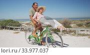 Senior Caucasian couple riding bikes on the beach. Стоковое видео, агентство Wavebreak Media / Фотобанк Лори