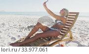 Caucasian woman taking a selfie on the beach. Стоковое видео, агентство Wavebreak Media / Фотобанк Лори