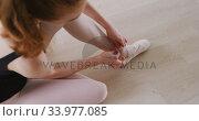 Купить «Caucasian female ballet dancer sitting on the floor in the studio and tying her ballet shoes», видеоролик № 33977085, снято 24 октября 2019 г. (c) Wavebreak Media / Фотобанк Лори