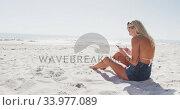 Caucasian woman using her smartphone on the beach. Стоковое видео, агентство Wavebreak Media / Фотобанк Лори