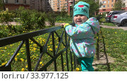 Купить «Toddler girl holds the rails while standing on urban courtyard of apartment house or condominium», видеоролик № 33977125, снято 10 июня 2020 г. (c) Кекяляйнен Андрей / Фотобанк Лори