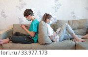 Pre-teen children gaming online using cellphones while sitting at home, kids wearing facial masks, sitting back to back on couch. Стоковое видео, видеограф Кекяляйнен Андрей / Фотобанк Лори