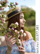 Купить «A beautiful girl in a blue dress and a straw hat holds a flowering branch of an Apple tree and looks into the distance», фото № 33977381, снято 29 мая 2020 г. (c) Максим Мицун / Фотобанк Лори