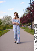 Купить «A beautiful girl in a blue dress and a straw hat walks along an empty Boulevard in the city garden.», фото № 33977389, снято 29 мая 2020 г. (c) Максим Мицун / Фотобанк Лори