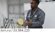 Купить «African American male car mechanic working and  checking and connecting a tool», видеоролик № 33984225, снято 6 ноября 2019 г. (c) Wavebreak Media / Фотобанк Лори