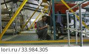 African American male car mechanic kneeling in a warehouse and using a tablet . Стоковое видео, агентство Wavebreak Media / Фотобанк Лори
