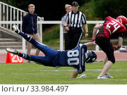 Berlin, Germany, American Football player holds on to the jersey of an opponent as he falls (2019 год). Редакционное фото, агентство Caro Photoagency / Фотобанк Лори