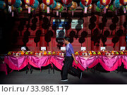 Singapore, Republic of Singapore, Man walks past lanterns and offerings at the Buddha Tooth Relic Temple (2019 год). Редакционное фото, агентство Caro Photoagency / Фотобанк Лори