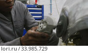 Купить «African American male car mechanic using an angle grinder on the side of a car », видеоролик № 33985729, снято 6 ноября 2019 г. (c) Wavebreak Media / Фотобанк Лори
