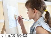 eight-year-old girl draws a brush pattern on an easel. Стоковое фото, фотограф Иванов Алексей / Фотобанк Лори