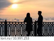 Купить «Двое молодых людей беседуют стоя на закате на фоне морского пейзажа», фото № 33991253, снято 22 марта 2020 г. (c) Иванов Алексей / Фотобанк Лори
