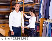 Купить «Young Chinese woman taking measurements handsome businessman for», фото № 33991685, снято 7 июля 2020 г. (c) Яков Филимонов / Фотобанк Лори