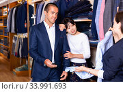 Young couple in love looking for mens shirt in clothing store, listening to recommendations of saleswoman. Стоковое фото, фотограф Яков Филимонов / Фотобанк Лори