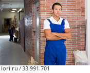 Portrait of young male worker during doing finishing work in room. Стоковое фото, фотограф Яков Филимонов / Фотобанк Лори