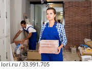 Man and woman in work overalls carrying bricks during finishing work in room of public space. Стоковое фото, фотограф Яков Филимонов / Фотобанк Лори