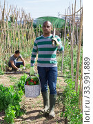 Купить «Indian man professional gardener holding basket with harvest», фото № 33991889, снято 25 мая 2020 г. (c) Яков Филимонов / Фотобанк Лори