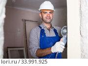 Worker in helmet is sawing wall with circular saw. Стоковое фото, фотограф Яков Филимонов / Фотобанк Лори