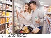 Portrait of young man with girlfriend choosing dairy products in supermarket. Стоковое фото, фотограф Яков Филимонов / Фотобанк Лори