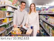 Купить «Happy man and woman with shopping cart», фото № 33992633, снято 7 ноября 2019 г. (c) Яков Филимонов / Фотобанк Лори