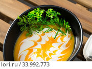 Купить «Recipe of pumpkin soup puree with ginger root - roast pumpkin in olive oil, beat in blender with vegetable broth. Add whisked cream with garlic and ginger. Serve with greens», фото № 33992773, снято 5 августа 2020 г. (c) Яков Филимонов / Фотобанк Лори