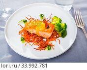 Steak of fried salmon with smoked carrots, broccoli, cucumbers and fig on plate. Стоковое фото, фотограф Яков Филимонов / Фотобанк Лори