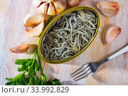 Open tin can of pickled eels and garlic with greens at table. Стоковое фото, фотограф Яков Филимонов / Фотобанк Лори