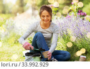 woman filling pots with soil at summer garden. Стоковое фото, фотограф Syda Productions / Фотобанк Лори