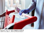 Купить «hand cleaning shopping cart handle with wet wipe», фото № 33993037, снято 30 апреля 2020 г. (c) Syda Productions / Фотобанк Лори