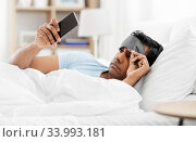 sleepy indian man with smartphone lying in bed. Стоковое фото, фотограф Syda Productions / Фотобанк Лори