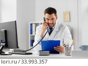 male doctor calling on desk phone at hospital. Стоковое фото, фотограф Syda Productions / Фотобанк Лори