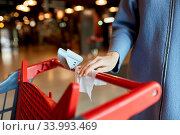 Купить «hand cleaning shopping cart handle with wet wipe», фото № 33993469, снято 30 апреля 2020 г. (c) Syda Productions / Фотобанк Лори