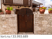 Wooden gate and stone fence in front of house in Cyprus (2019 год). Стоковое фото, фотограф Володина Ольга / Фотобанк Лори