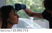 Young woman brow master wipes out eyebrows of the model. Стоковое видео, видеограф Константин Шишкин / Фотобанк Лори