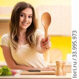 Купить «Young woman preparing salad at home in kitchen», фото № 33995973, снято 12 июня 2018 г. (c) Elnur / Фотобанк Лори