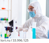 Купить «Young chemist student working in lab on chemicals», фото № 33996125, снято 27 апреля 2018 г. (c) Elnur / Фотобанк Лори