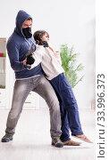 Купить «Armed man assaulting young woman at home», фото № 33996373, снято 15 декабря 2017 г. (c) Elnur / Фотобанк Лори