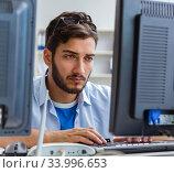 Купить «IT technician looking at IT equipment», фото № 33996653, снято 6 июля 2017 г. (c) Elnur / Фотобанк Лори