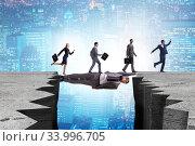 Businessman acting as a bridge in support concept. Стоковое фото, фотограф Elnur / Фотобанк Лори