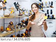 Купить «Female customer showing desired shoe in boutique», фото № 34016605, снято 9 июля 2020 г. (c) Яков Филимонов / Фотобанк Лори